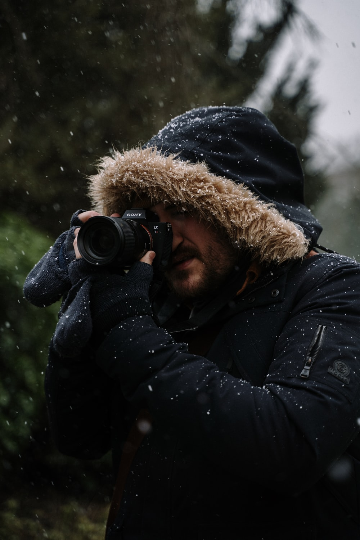 person in black and brown parka jacket holding black dslr camera