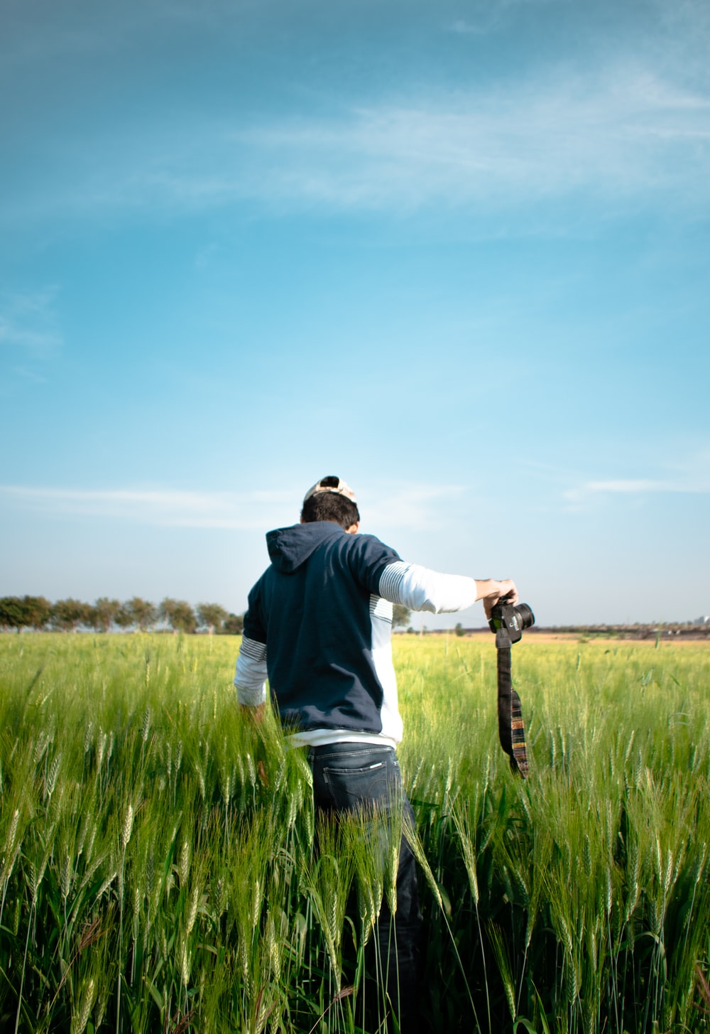 man in black jacket holding black dslr camera standing on green grass field during daytime