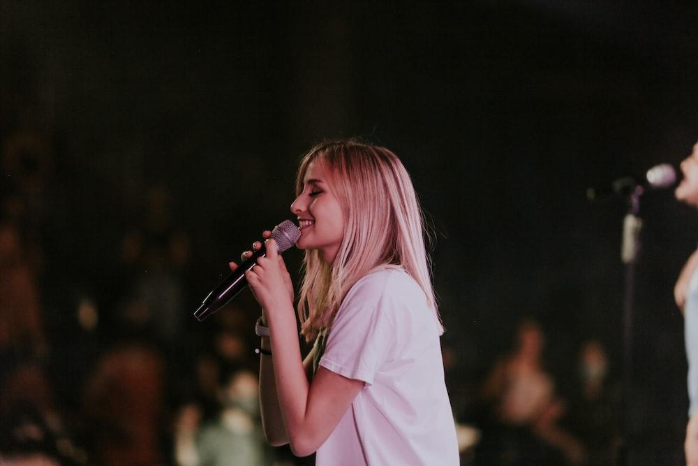 woman in white t-shirt singing