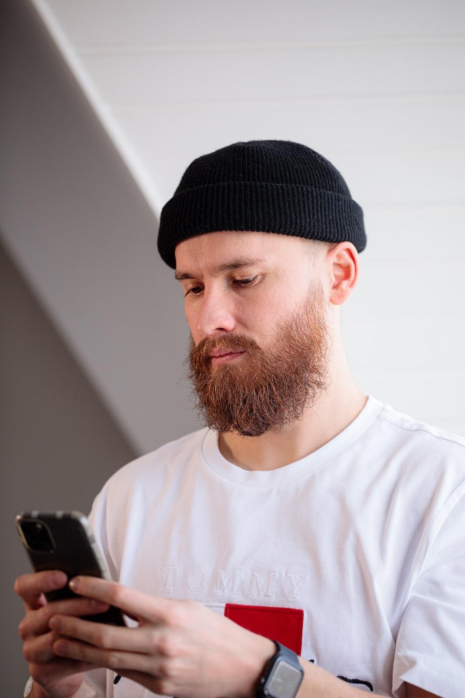 man in white crew neck shirt wearing black knit cap