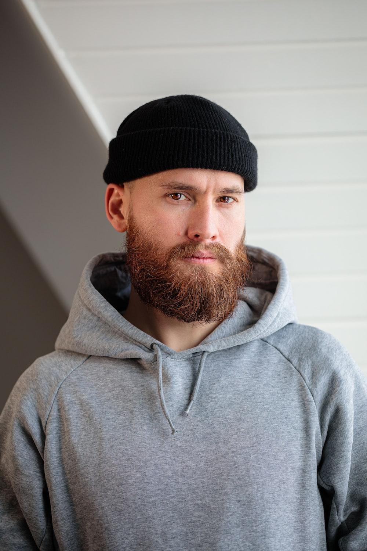 man in gray hoodie wearing black knit cap