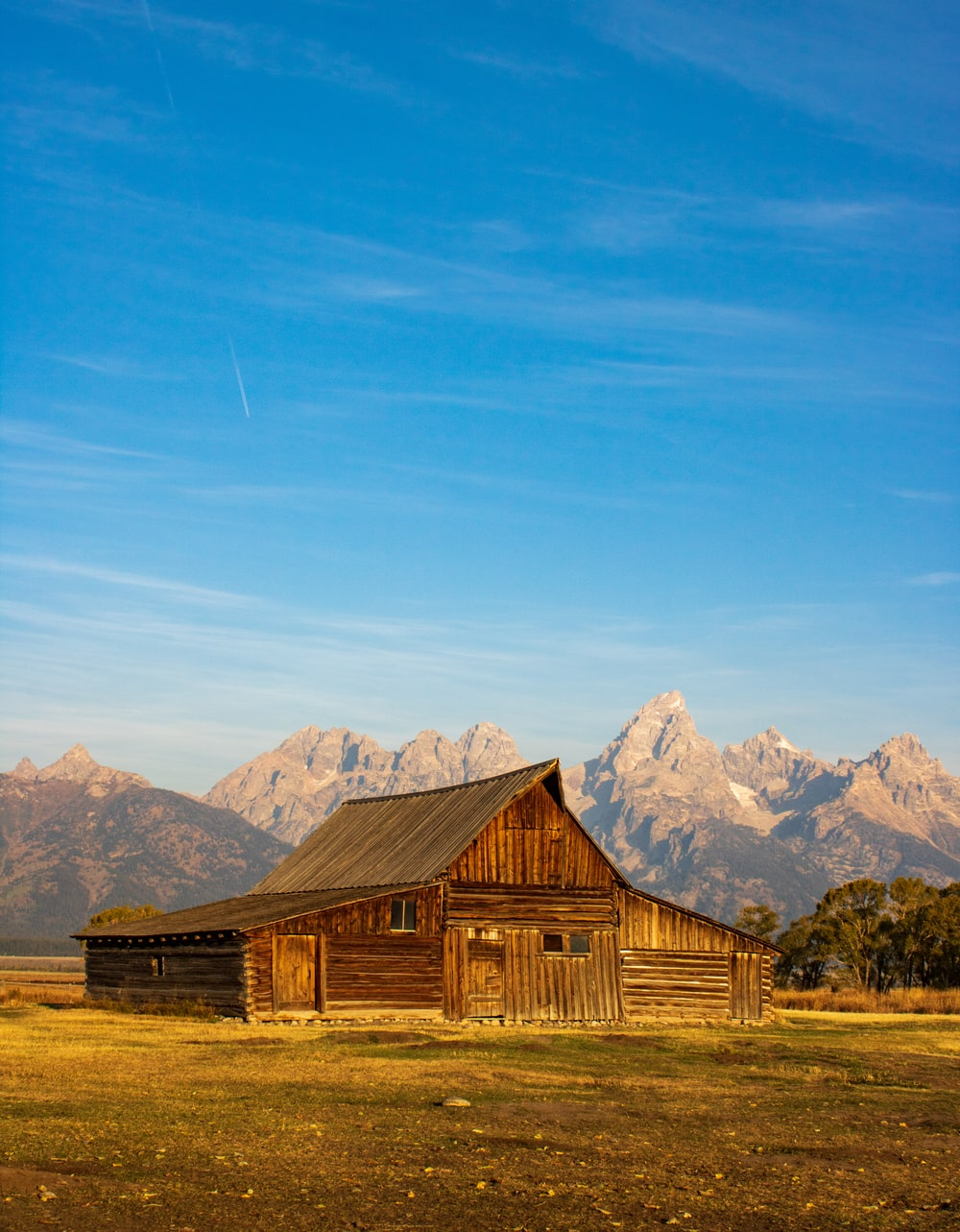 brown wooden house on brown grass field near mountain under blue sky during daytime
