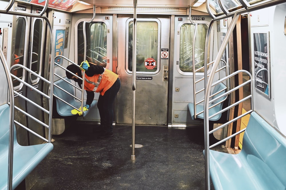 man in orange jacket and blue pants standing beside white train