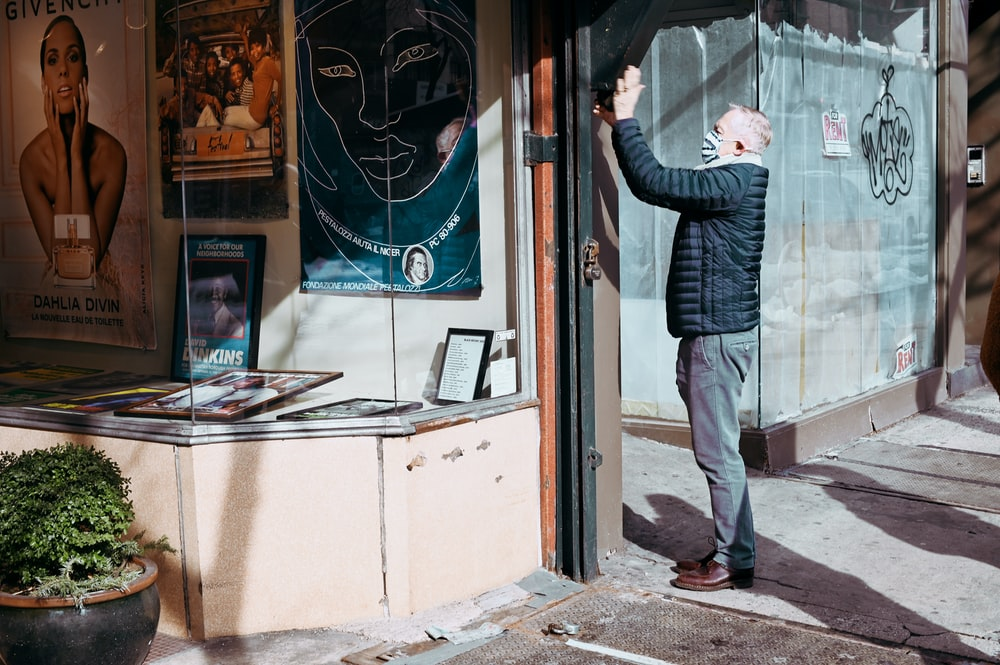 man in black and white striped long sleeve shirt and gray pants standing near glass window
