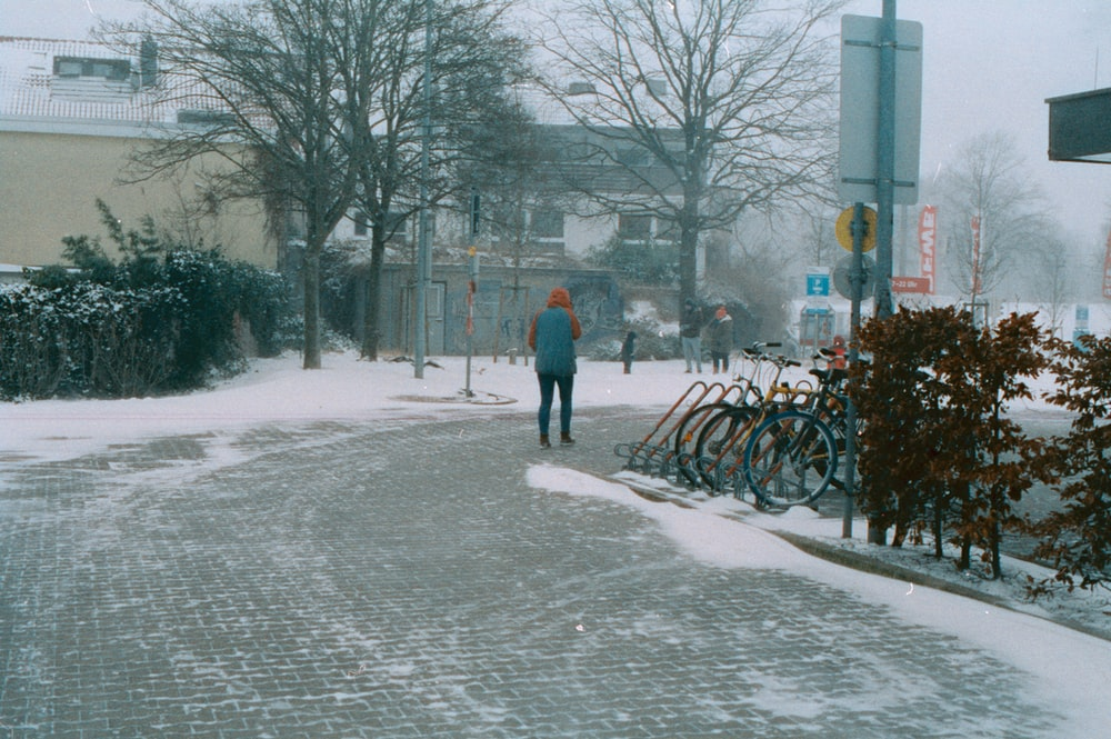 person in red jacket walking on snow covered road during daytime