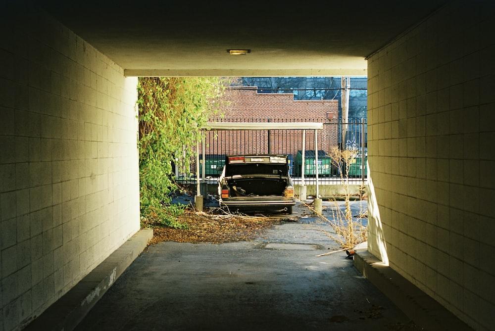 black metal bench beside brick wall