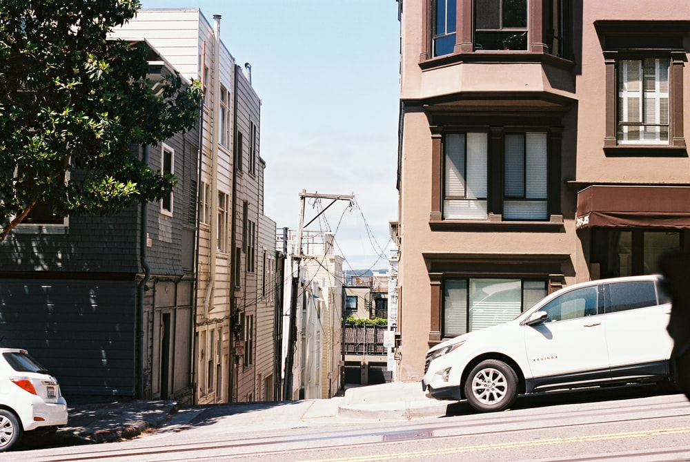white car parked beside brown concrete building during daytime