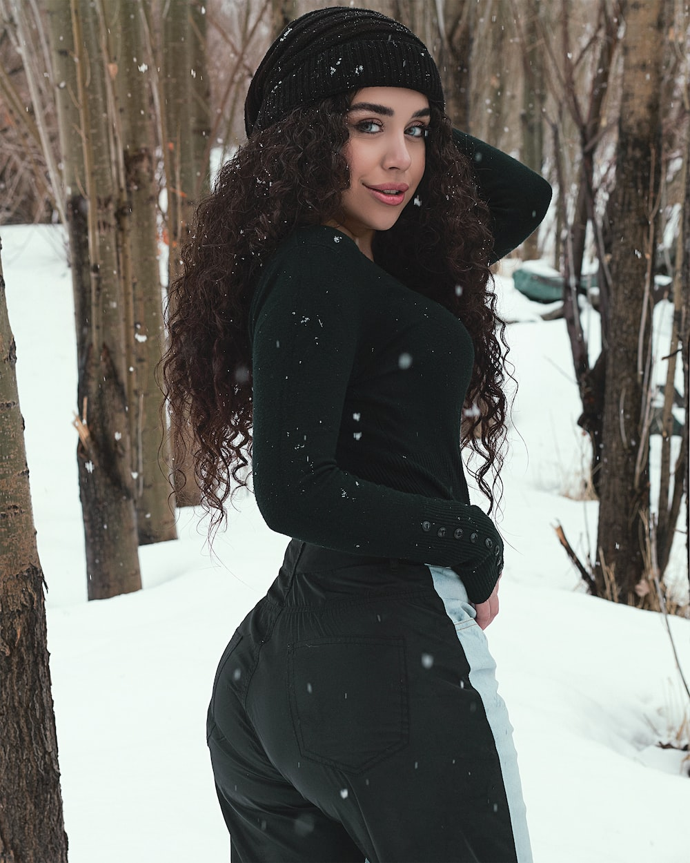 woman in black long sleeve dress standing on snow covered ground during daytime