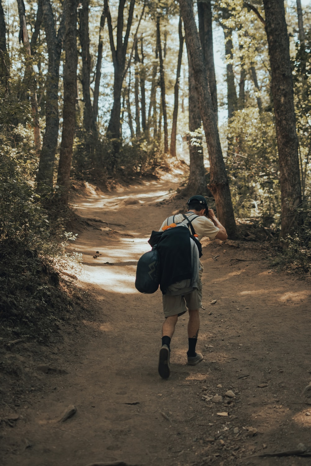 woman in blue jacket and black pants with backpack walking on dirt road between trees during