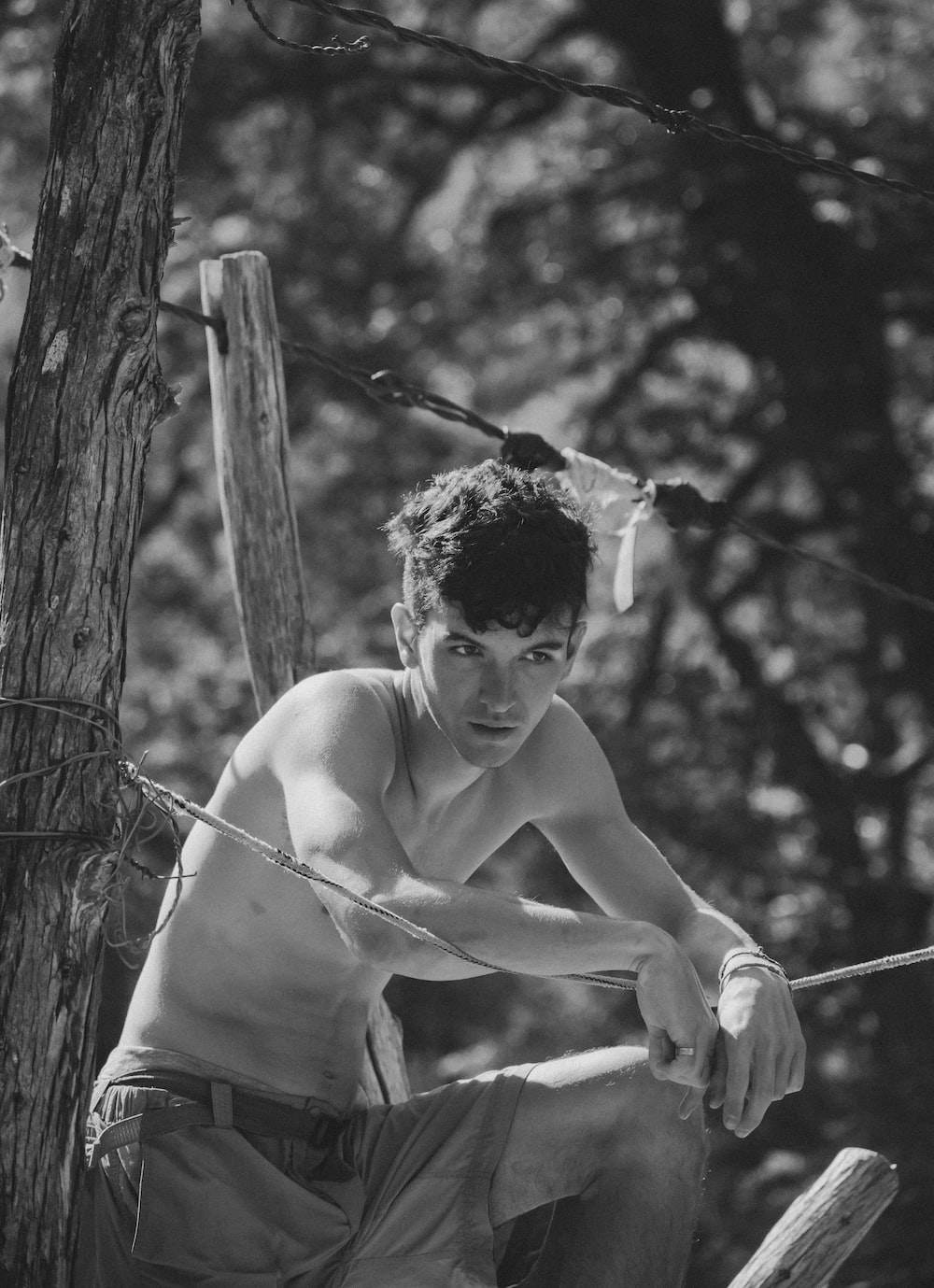 topless man in shorts holding rope