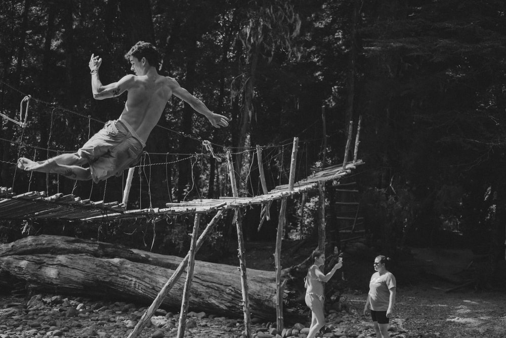 grayscale photo of 3 men climbing on wooden fence
