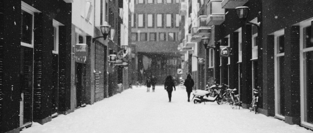people walking on snow covered road near buildings during daytime