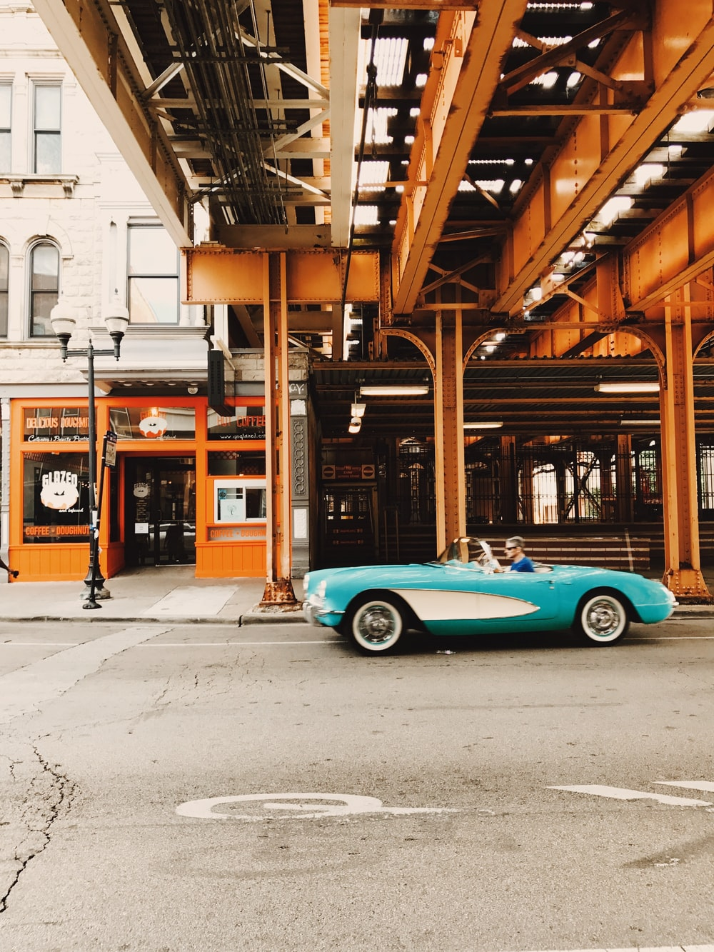 teal coupe parked beside brown wooden building during daytime