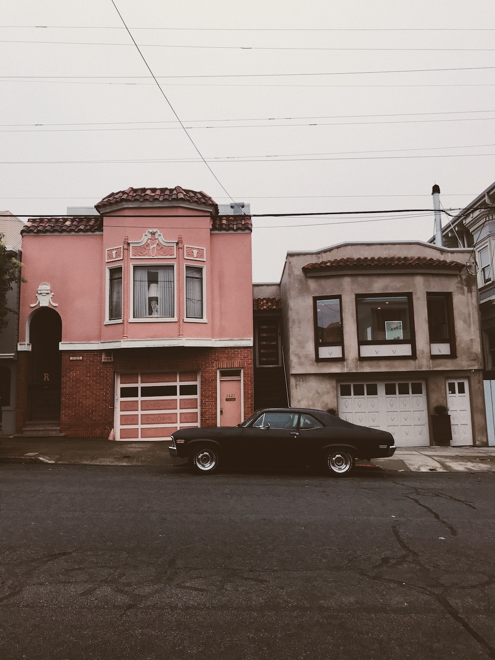 black coupe parked beside red concrete building during daytime