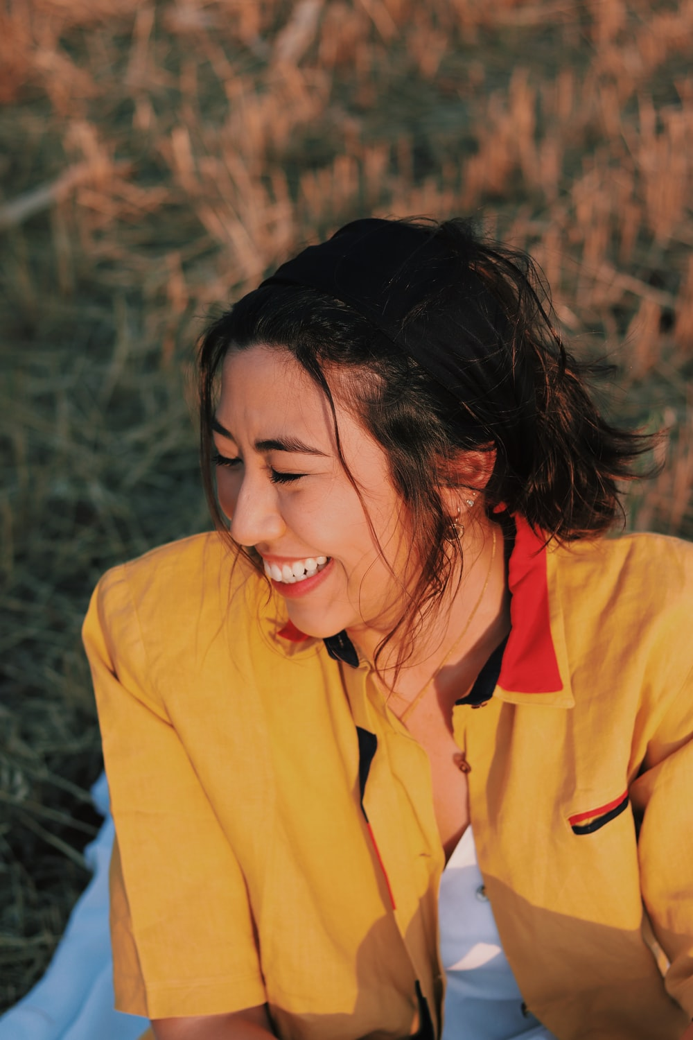 woman in yellow button up shirt smiling