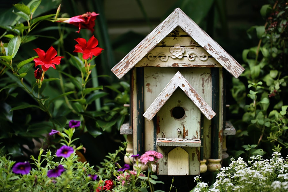 brown wooden birdhouse with red flowers