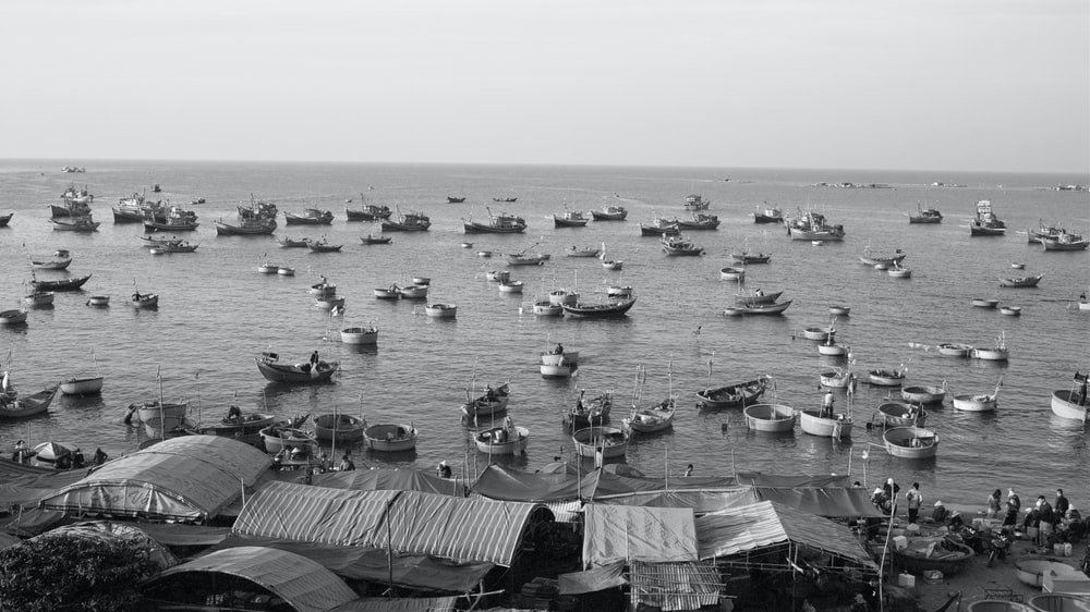 grayscale photo of boats on sea