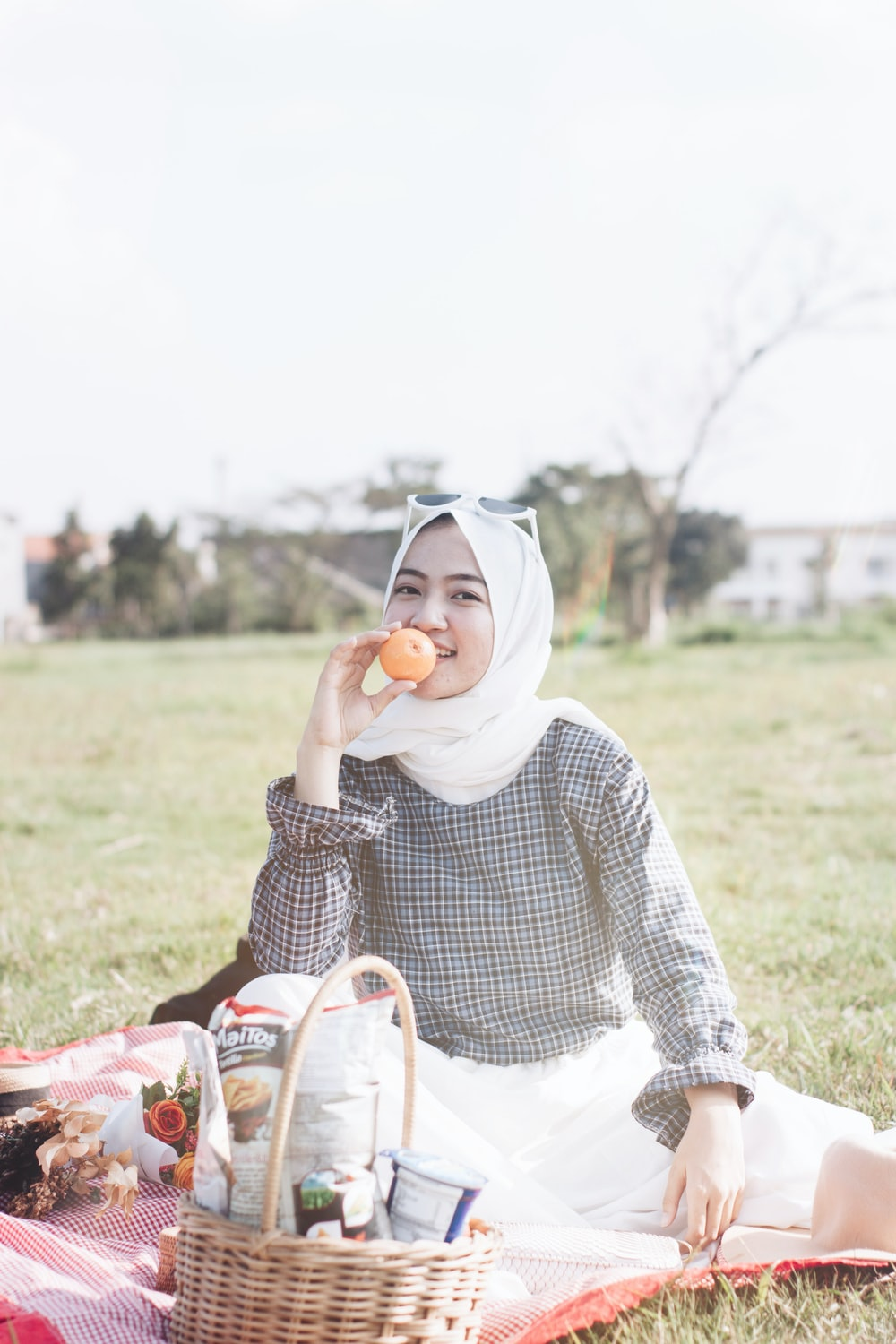 woman in white hijab and black and white long sleeve shirt sitting on green grass field