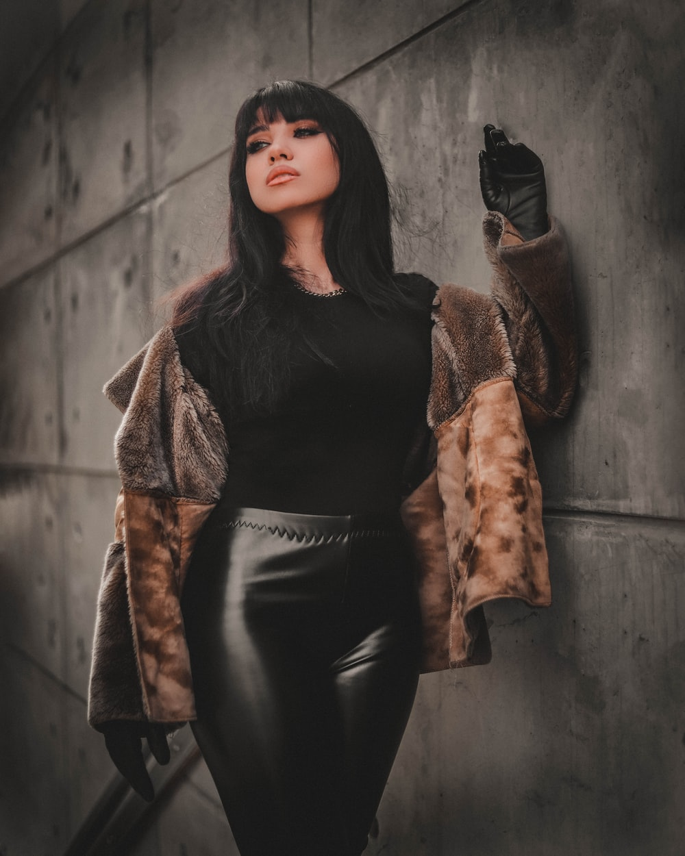 woman in black leather jacket and black pants leaning on wall