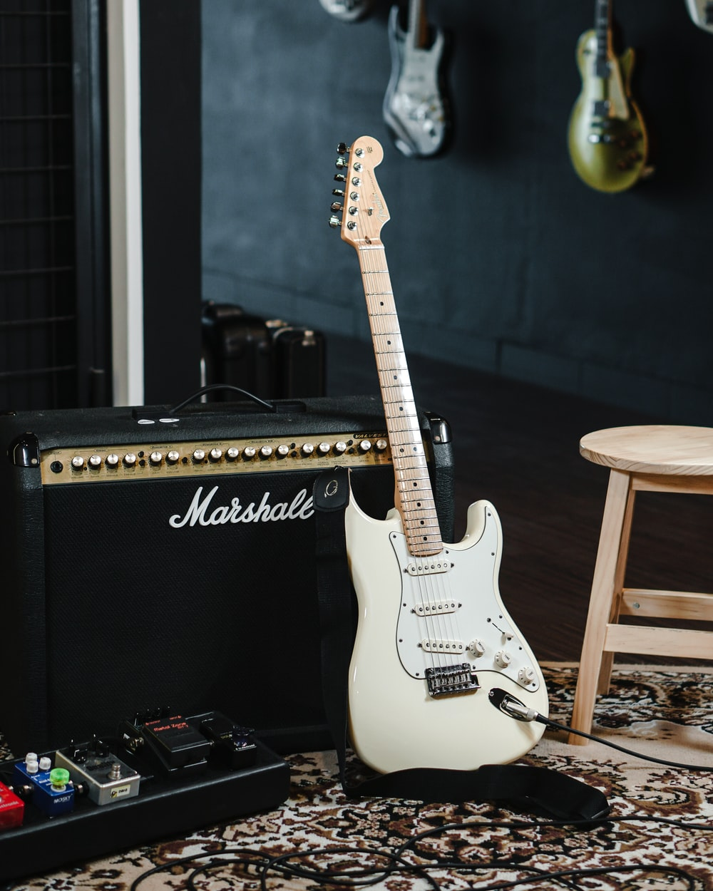 white and black stratocaster electric guitar on black guitar amplifier