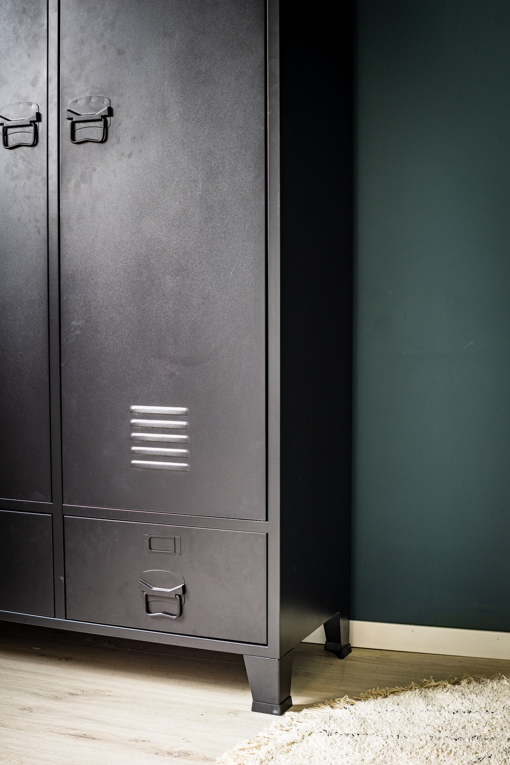 black wooden cabinet beside white wall