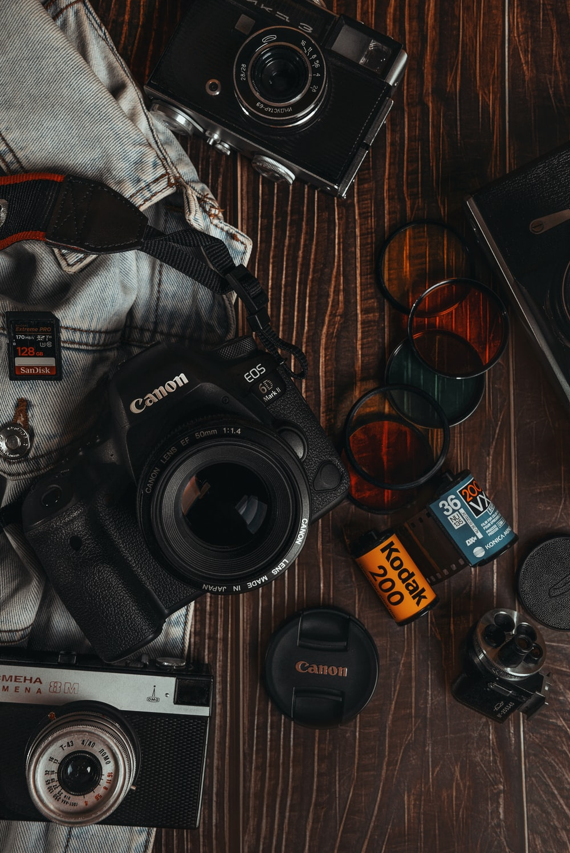 black nikon dslr camera beside black framed sunglasses
