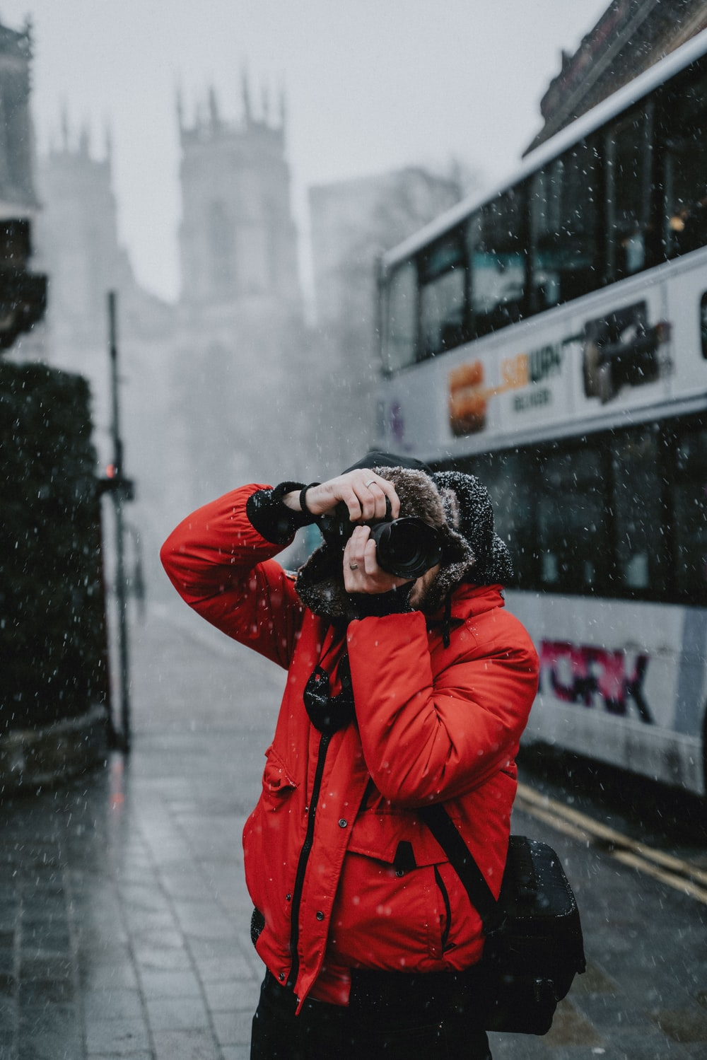 person in red jacket holding black dslr camera