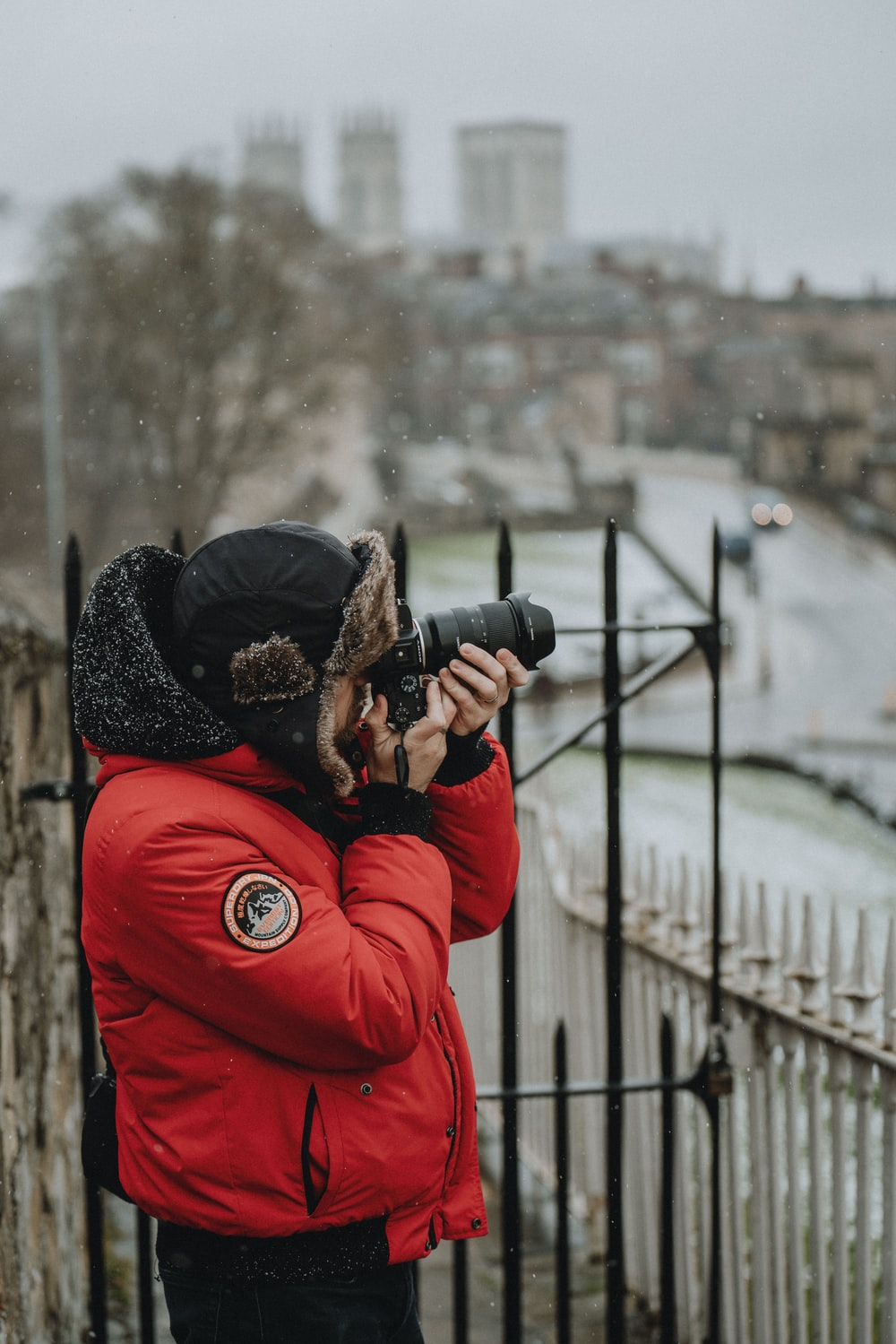 woman in red jacket holding black dslr camera