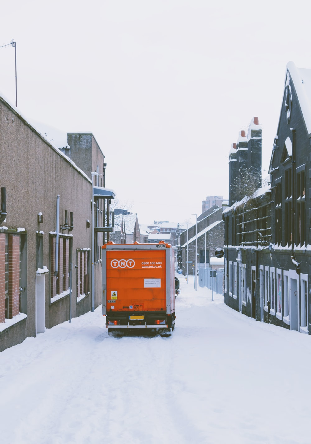 orange truck on snow covered road during daytime