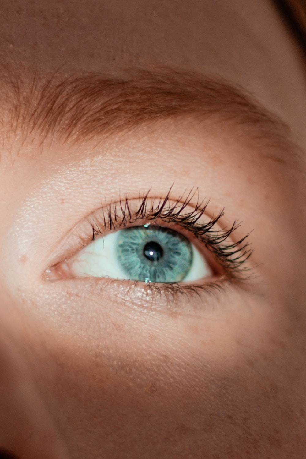 persons green eye in close up photography