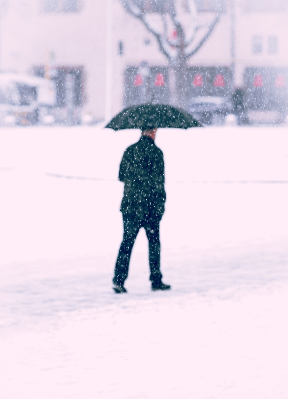 person in black jacket holding umbrella walking on snow covered ground during daytime