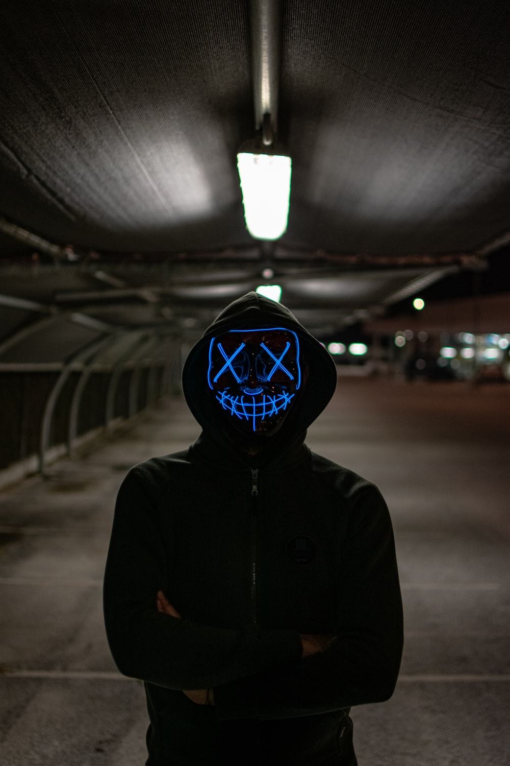 man in black hoodie wearing blue and white mask