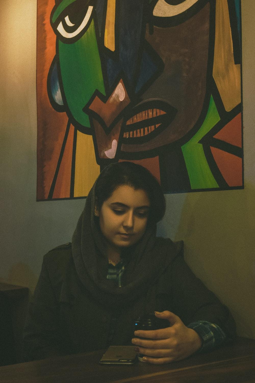 man in black hoodie standing beside wall with painting