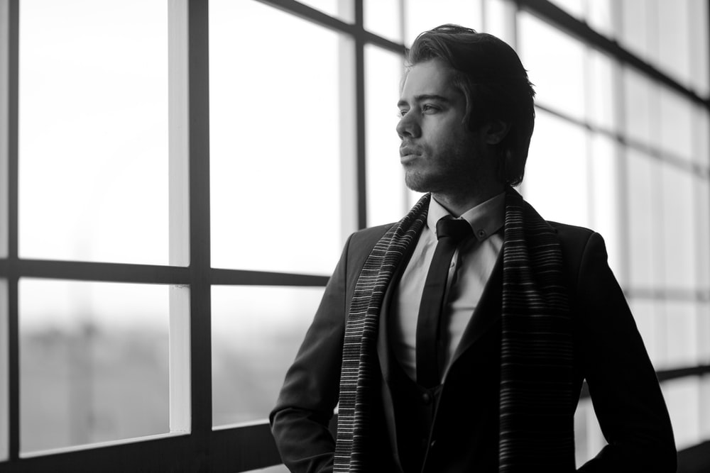 man in black and white suit standing near window