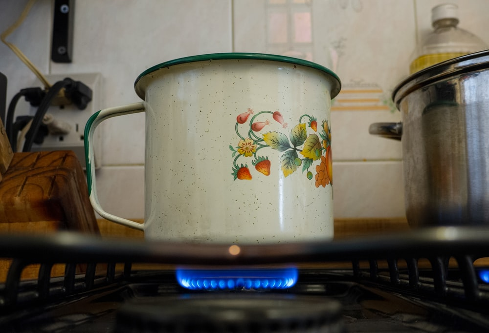 white and pink floral cooking pot on stove