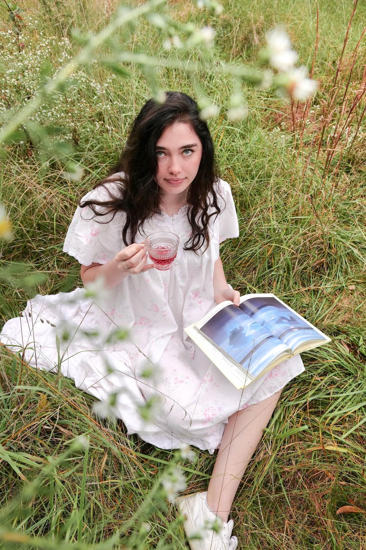 woman in white dress sitting on green grass field