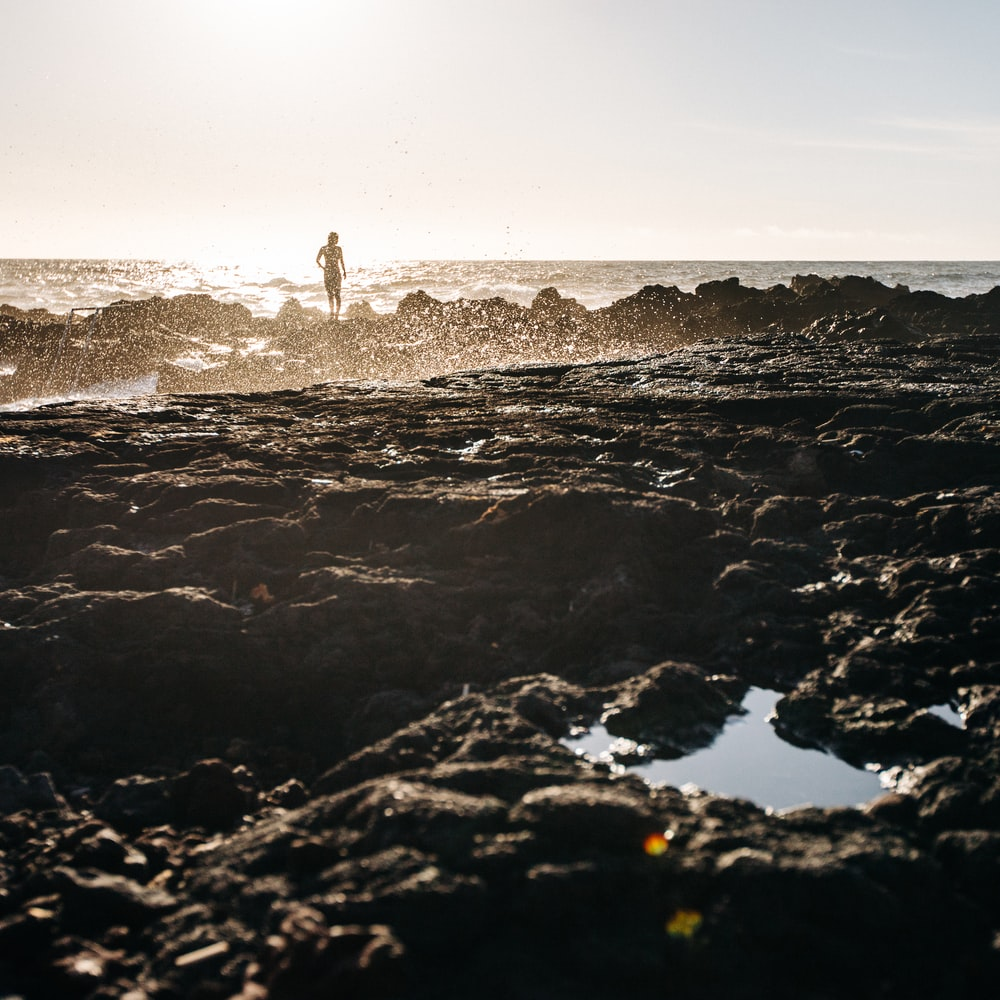 person standing on rock formation in front of ocean water during daytime