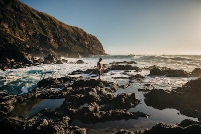 Ponta Delgada woman in white bikini standing on rocky shore during daytime