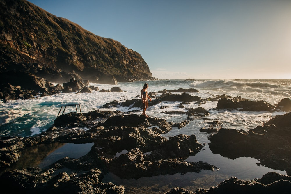 woman in white bikini standing on rocky shore during daytime