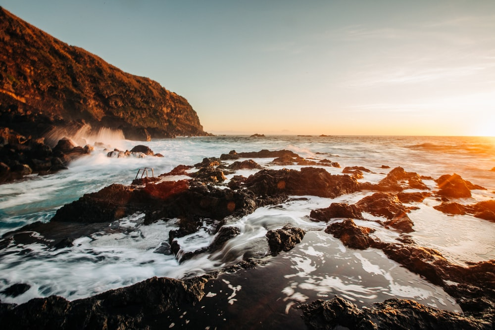 rocky shore with water waves during daytime