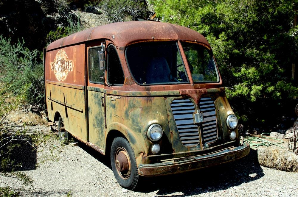 brown van on gray asphalt road during daytime