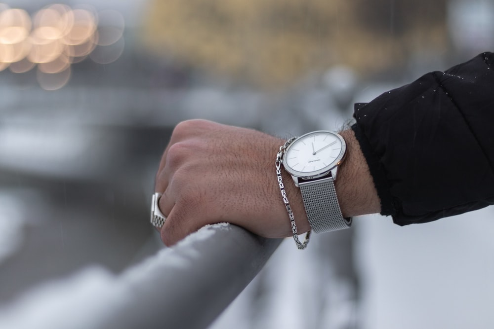 person wearing silver round analog watch with black leather strap