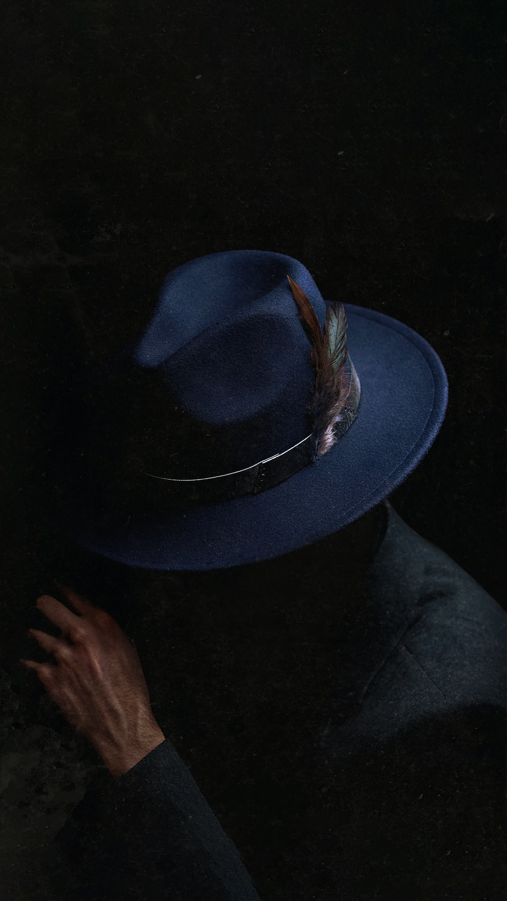 person holding black fedora hat