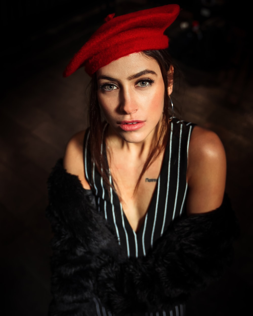 woman in black fur vest and red hat