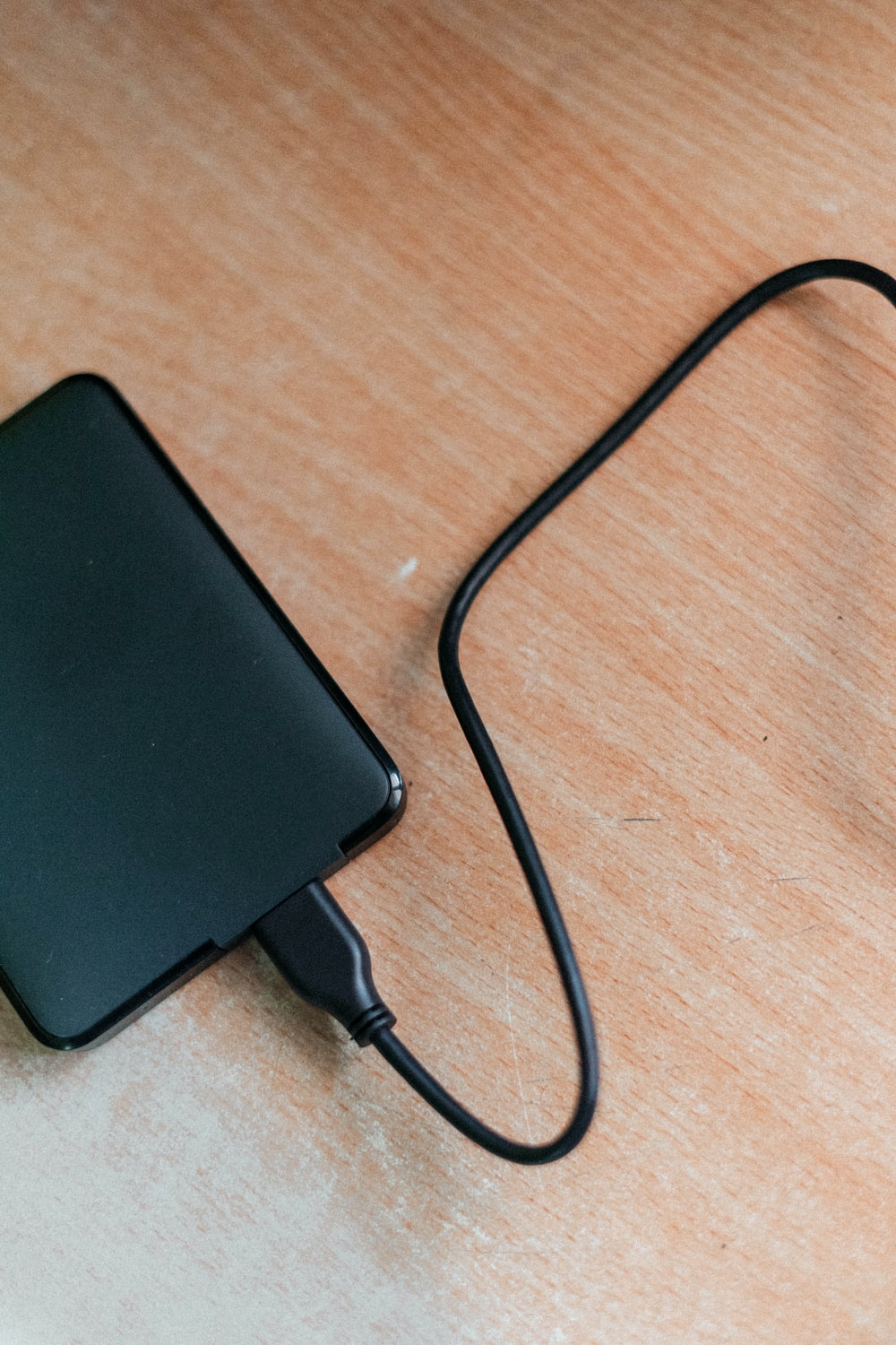 black power bank on brown wooden table