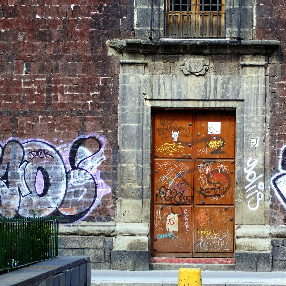 brown wooden door with white and blue graffiti