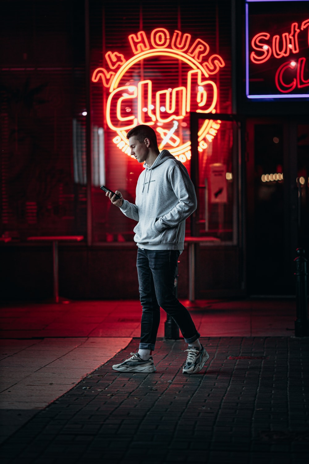 man in gray hoodie standing in front of red neon light signage