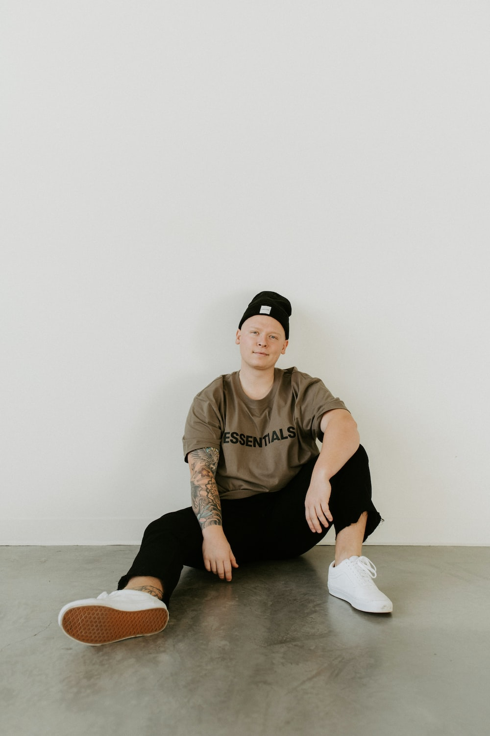 man in brown crew neck t-shirt and black pants sitting on floor