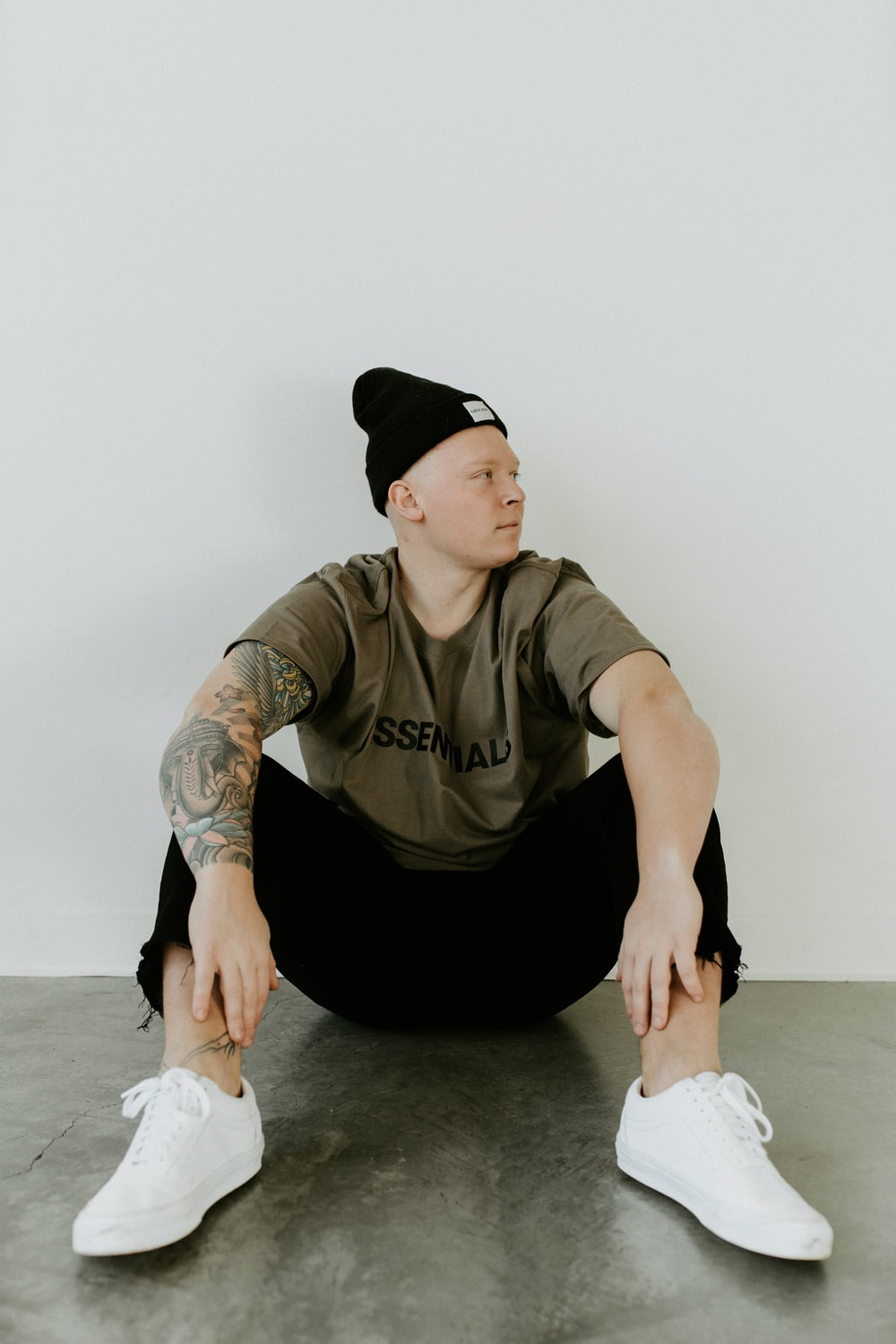 man in black crew neck t-shirt and black pants sitting on floor