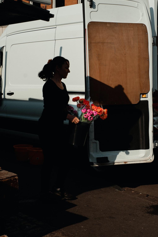 woman in black dress holding bouquet of flowers
